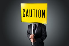 Businessman holding a caution sign Royalty Free Stock Photo