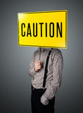 Businessman holding a caution sign Royalty Free Stock Images