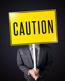 Businessman holding a caution sign. Businessman standing and holding a yellow caution sign in front of his head stock photo