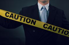 A businessman with caution tape. A businessman holding caution tape across chest Stock Images