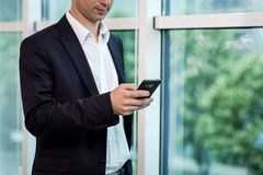 Businessman holding a cell phone and writing sms message in offi. Ce,businessman use mobile smart phone,Close up of a man using mobile phone,Young businessman Royalty Free Stock Photography