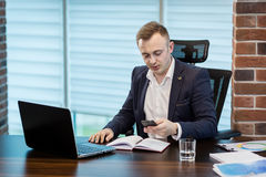 Businessman holding a cell phone and writing sms message in offi. Ce,businessman use mobile smart phone,Close up of a man using mobile phone,Young businessman Royalty Free Stock Photo