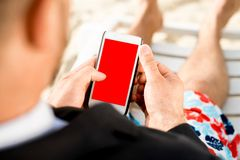 Businessman holding cellphone on the beach Stock Images