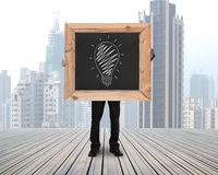 Businessman holding chalkboard with hand-drawn ideas equal money. Concept on skyscraper cityscape and wooden floor background royalty free stock photos
