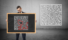 A businessman holding a chalkboard with a picture of a solved maze, unseeing a new maze behind him. royalty free stock photo