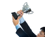 Businessman holding a champion silver trophy on white background. Businessman holding a champion silver trophy isolated on white background with clipping path stock photo