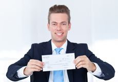 Businessman holding cheque Royalty Free Stock Photos