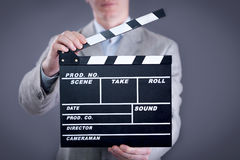 Businessman holding clapper board Stock Images