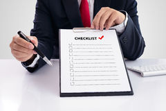 Businessman holding clipboard with checklist against Royalty Free Stock Photos