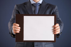 Businessman holding a clipboard with empty sheet of paper Stock Image