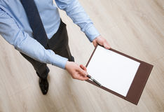 Businessman holding a clipboard with empty sheet of paper and pr Stock Images