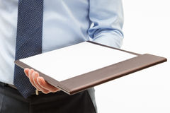 Businessman holding a clipboard with empty sheet of paper Royalty Free Stock Photography