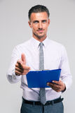 Businessman holding clipboard and showing gun gesture Stock Photography