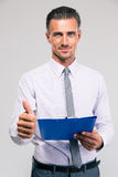 Businessman holding clipboard and showing thumb up Royalty Free Stock Photo