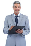Businessman holding clipboard and taking notes Royalty Free Stock Images