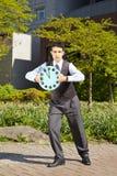 Businessman holding a clock Stock Photos