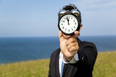 Businessman holding clock. And standing on the field Royalty Free Stock Photos