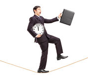 Businessman holding clock and briefcase and walking on a rope. Full length portrait of a businessman holding clock and briefcase and walking on a rope isolated Royalty Free Stock Photography