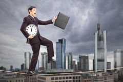 Businessman holding clock and briefcase, walking on a rope Royalty Free Stock Photography
