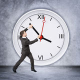 Businessman holding clock hand Stock Image