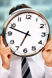Businessman holding clock over face Royalty Free Stock Photo