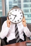 Businessman holding clock over face Royalty Free Stock Photography