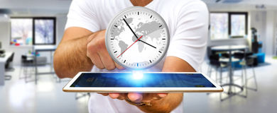 Businessman holding a clock over his digital tablet. Businessman holding a big white timer over his digital tablet Royalty Free Stock Image