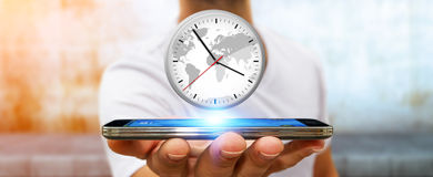 Businessman holding a clock over his mobile phone. Businessman holding a big white timer over his mobile phone Stock Images