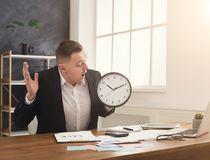 Businessman holding clock and pointing on it. Confused businessman in suit holding clock and looking at it. Portrait of man with watches at office. Time Royalty Free Stock Images