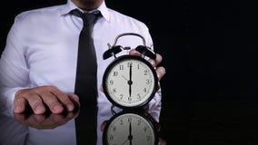 Businessman Holding Clock Pointing at Six O& x27;Clock