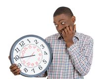 Businessman holding clock pressured by lack of time Stock Photo