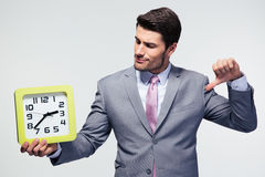 Businessman holding clock and showing thumb down Stock Photos