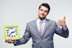 Businessman holding clock and showing thumb up Stock Image