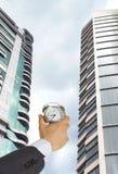 Businessman holding a clock Stock Photo