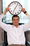 Businessman holding clock to his head Royalty Free Stock Images