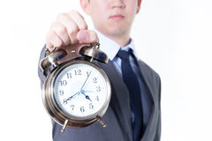 Businessman holding a clock in unpleasant face expression - business and time concept Royalty Free Stock Photos