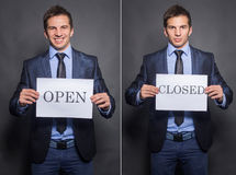 Businessman holding closed and open signs Royalty Free Stock Photo