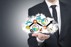 A businessman is holding a cloud with the business flowchart on the open palm. Royalty Free Stock Image