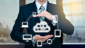 Businessman holding a cloud connected to many objects on virtual screen concept about the internet of things Stock Image