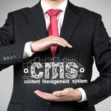 Businessman holding cms symbol Royalty Free Stock Photo