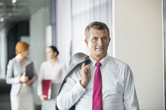 Businessman holding coat over shoulder with female colleagues in background at office Royalty Free Stock Images