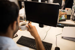 Businessman holding coffee cup by desktop pc in office. Cropped image of businessman holding coffee cup by desktop pc in office stock photo