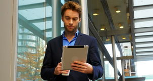 Businessman holding coffee cup and using digital tablet stock footage