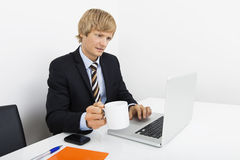 Businessman holding coffee cup while using laptop at desk in office Royalty Free Stock Images