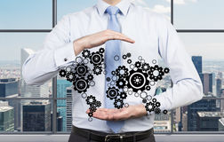 Businessman holding cogs Stock Image