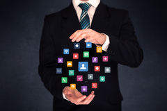 Businessman holding colorful applications Royalty Free Stock Photos