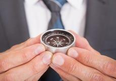 Businessman holding compass Stock Photos
