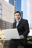 Businessman holding computer laptop in stress outdoors on financial district Royalty Free Stock Photo