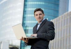 Businessman holding computer laptop working outdoors Stock Image