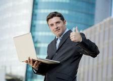 Businessman holding computer laptop working urban business outdoors Stock Photo